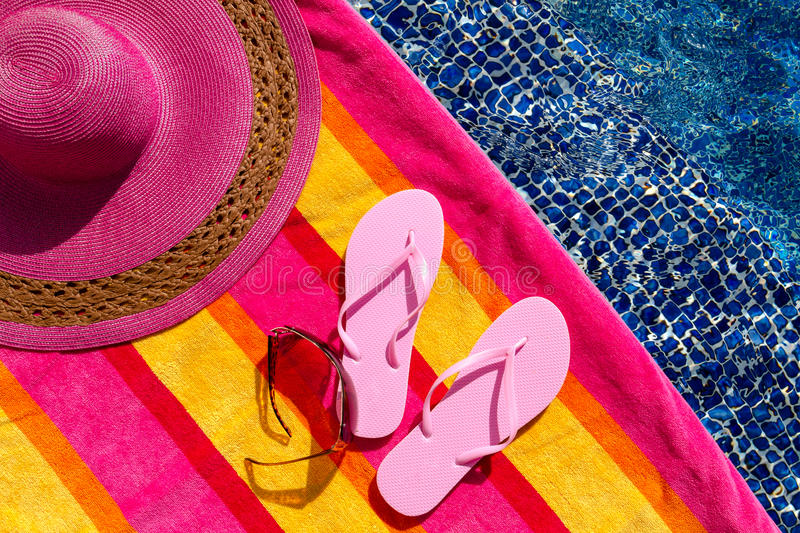 Flip Flops by the Pool. Pair of light pink flip flops by the pool on a bright orange, pink, red and yellow striped towel with sunglasses and big pink floppy hat stock photo