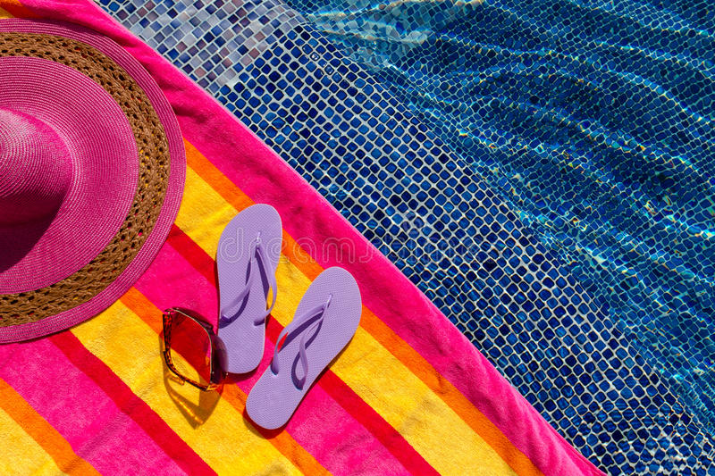 Flip Flops by the Pool. Pair of light purple flip flops by the pool on a bright orange, pink, red and yellow striped towel with sunglasses and big pink floppy stock image
