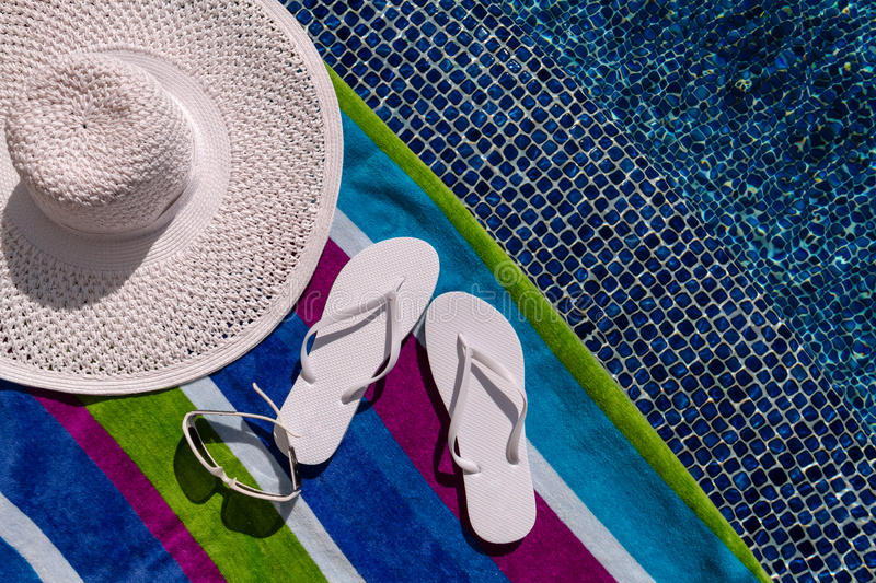 Flip Flops by the Pool. Pair of white flip flops by the pool on a bright blue, green, purple and white striped towel with sunglasses and big white floppy hat stock images