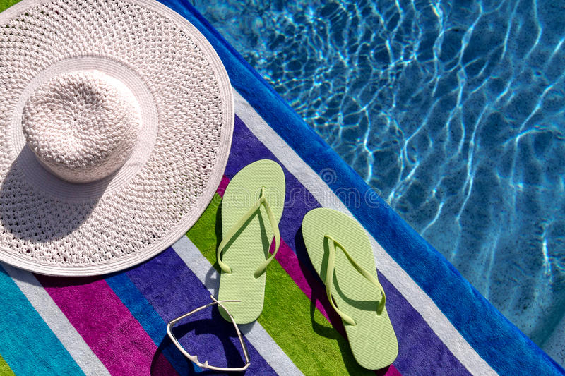 Flip Flops by the Pool. Pair of green flip flops by the pool on a bright blue, green, purple and white striped towel with sunglasses and big white floppy hat royalty free stock images