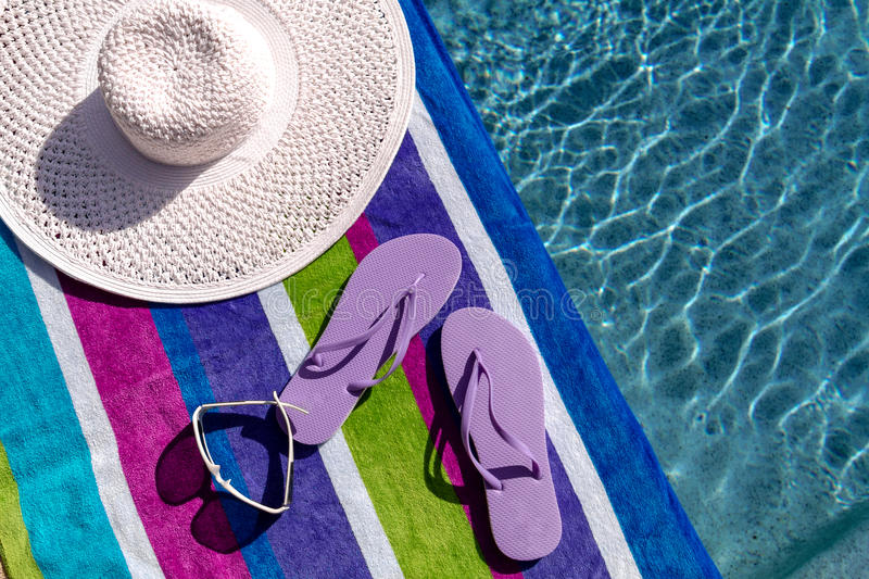 Flip Flops by the Pool. Pair of light purple flip flops by the pool on a bright blue, green, purple and white striped towel with sunglasses and big white floppy stock photography