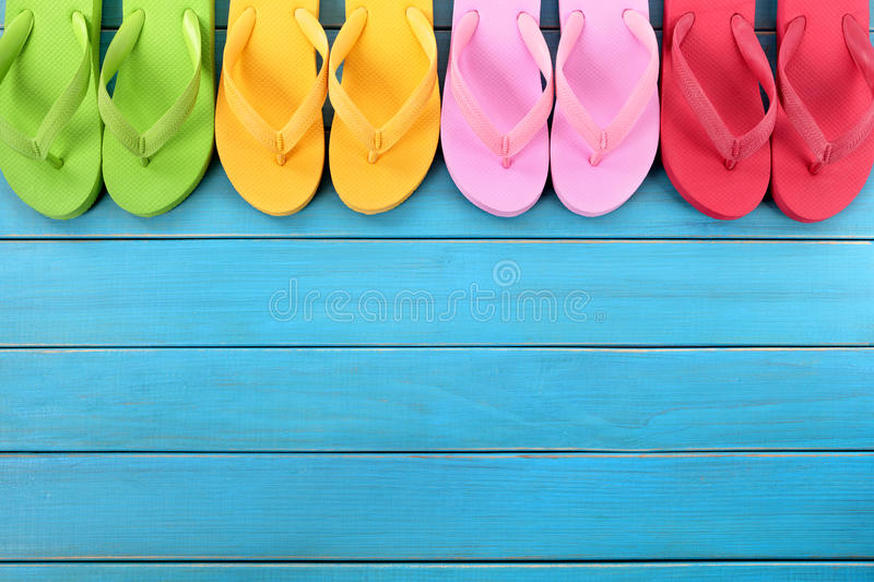 Flip flops in a row with blue beach decking, copy space. Row of colorful flip flops on old weathered blue painted beach decking. Space for copy royalty free stock photo
