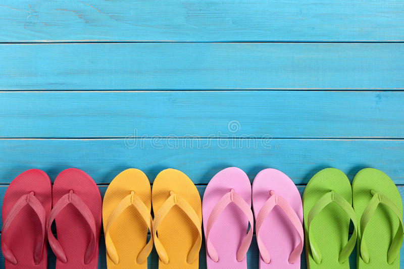 Flip flops in a row, copy space. Row of colorful flip flops on old weathered blue painted beach decking. Space for copy royalty free stock photo
