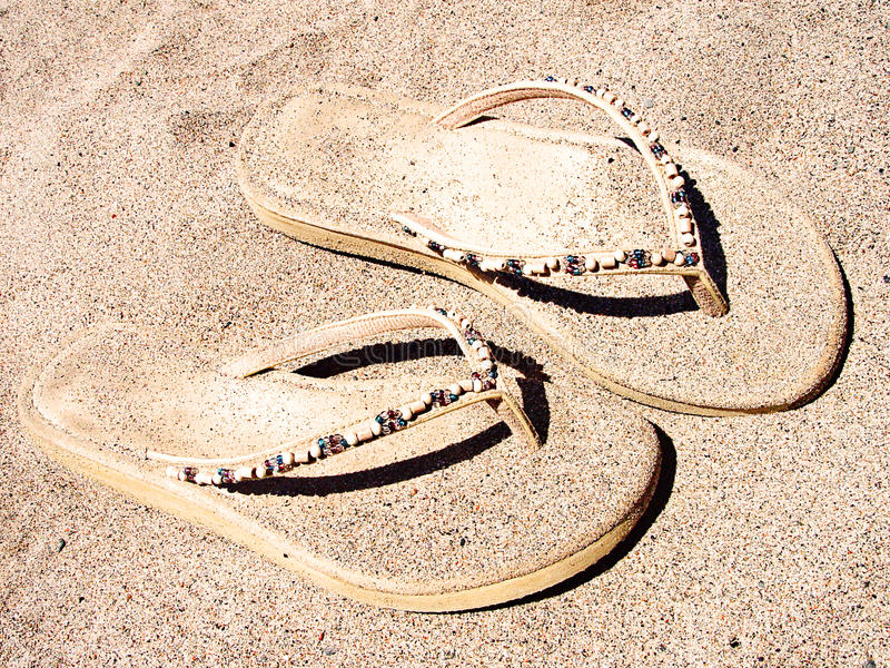 Flip flops in sand royalty free stock images