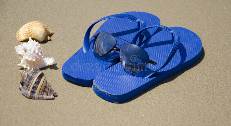 Flip flops on a sand. Blue flip-flops with seashells on beach's sand royalty free stock photography