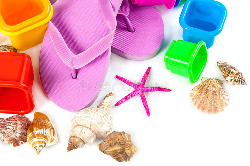 Flip flops, sand toys and seashells. Flip flops, sand toys and seashells isolated on a white background. The concept of a beach holiday stock photos