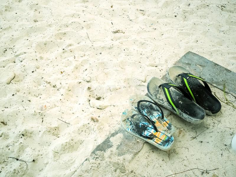 Flip flops on a sandy ocean beach. Flip-flops are a type of sandal, typically worn as a form of casual wear. They consist of a flat sole held loosely on the foot stock photography