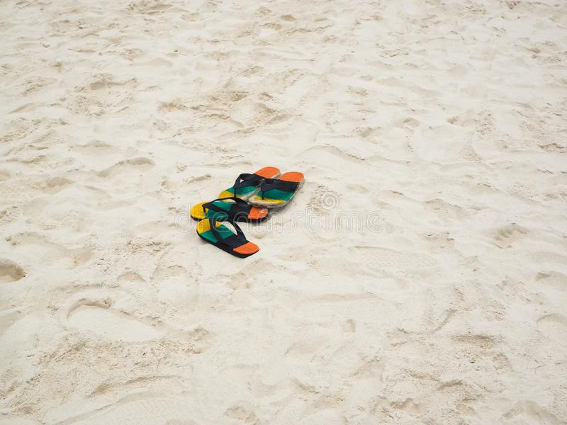 Flip flops on a sandy ocean beach. Flip-flops are a type of sandal, typically worn as a form of casual wear. They consist of a flat sole held loosely on the foot stock image