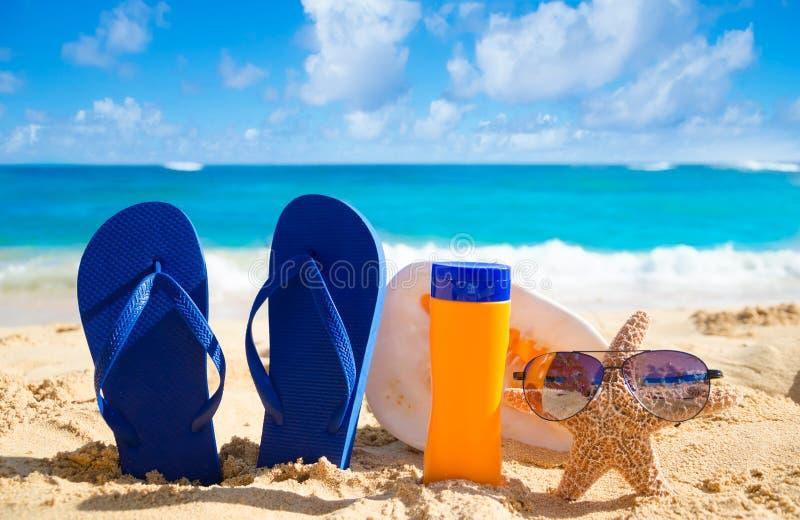 Flip flops, seashell, sunscreen and starfish with sunglasses on. Blue Flip flops, seashell, sunscreen and starfish with sunglasses on sandy beach in Hawaii stock photos