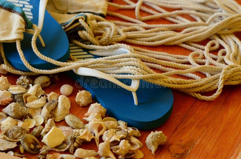 Flip-flops, shells and hammock net on wooden background stock photos