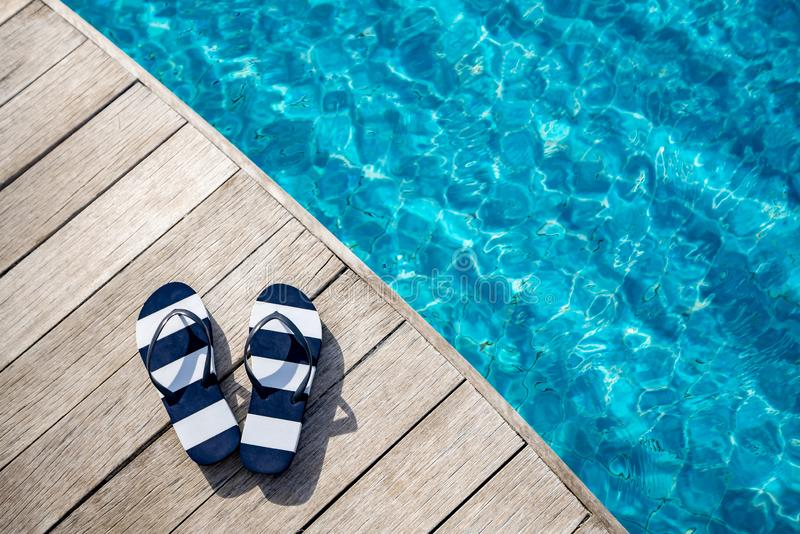 Flip flops  at the side of swimming pool, summer travel concept royalty free stock image