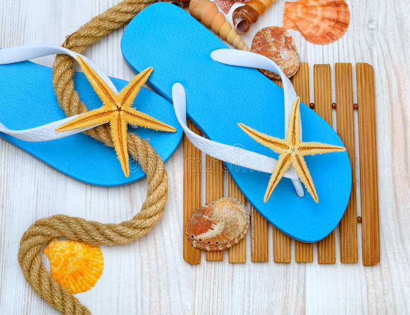 Flip-flops, starfish and seashells. Flip-flops, starfish and seashells on a wooden background royalty free stock photography