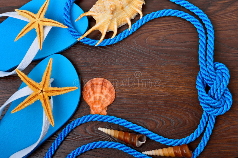 Flip-flops, starfish and seashells. Flip-flops, starfish and seashells on a wooden background royalty free stock images