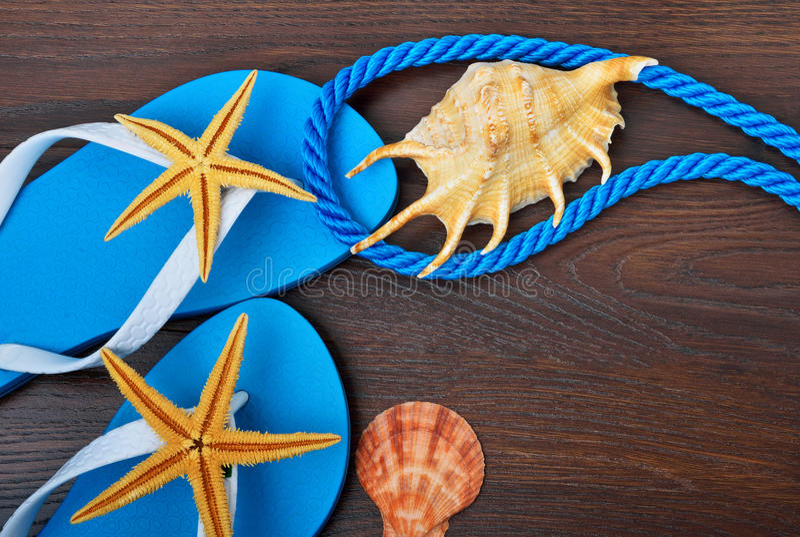Flip-flops, starfish and seashells. Flip-flops, starfish and seashells on a wooden background royalty free stock photos