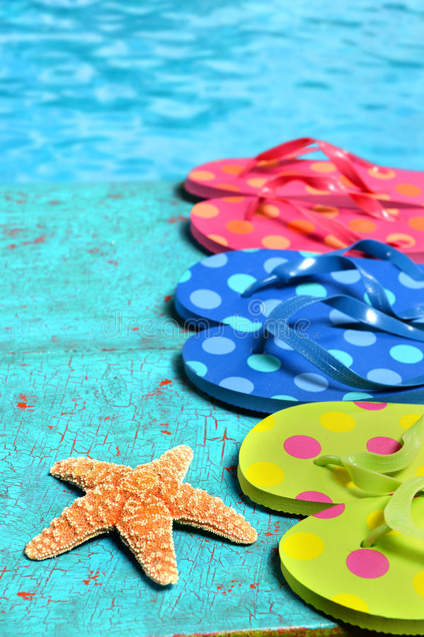 Flip Flops Starfish By Water. Flip flops and starfish on wood planks by the water stock images