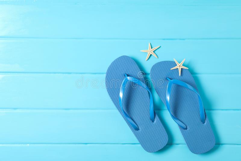Flip flops and starfishes on color wooden background, space for text and top view. Summer vacation royalty free stock photography