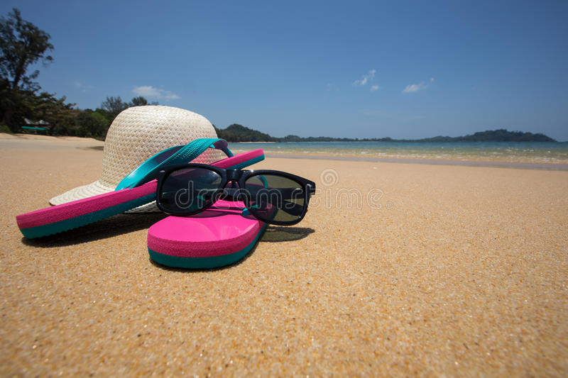 Flip flops, straw hat and sunglasses on tropical beach.  stock photos