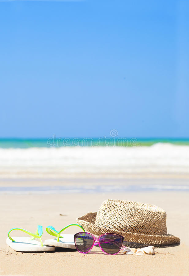 Flip flops straw hat and sunglasses on tropical royalty free stock image