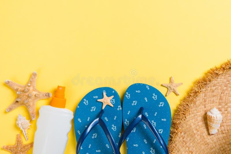 Flip Flops, Strohhut, Seesterne, Sonnenschutzflasche, Bodylotion Spray auf gelbem Hintergrund oben flaches Sommermeer stockfotografie