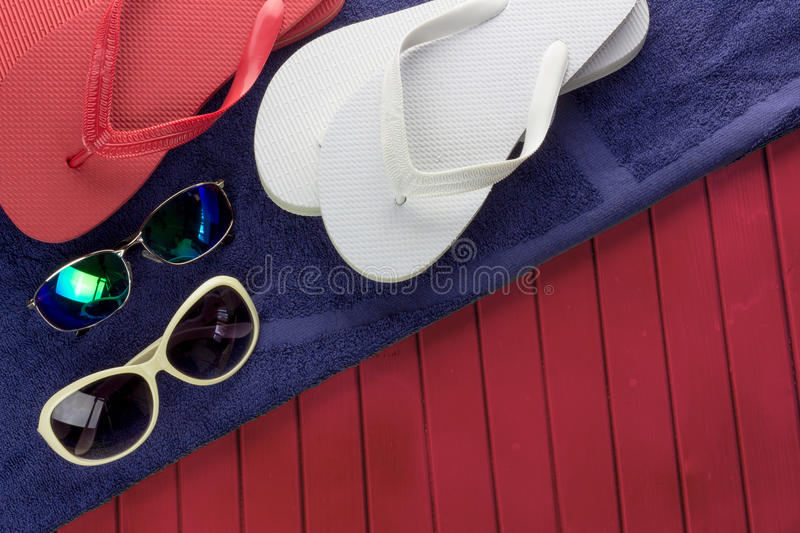 Flip flops and sunglasses. Colorful flip flops and sunglasses with purple towel on red deck royalty free stock photography