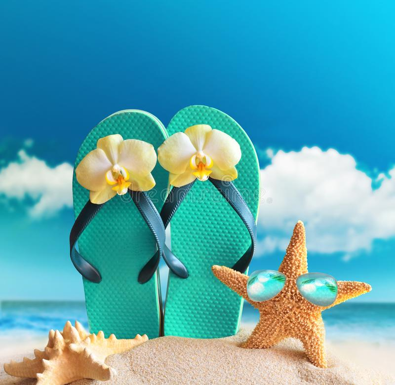 Flip-flops, sunglasses with starfish on summer beach royalty free stock image
