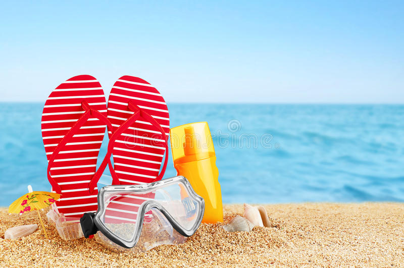 Flip-flops, sunscreen spray and diving masks on the beach. Shells royalty free stock image