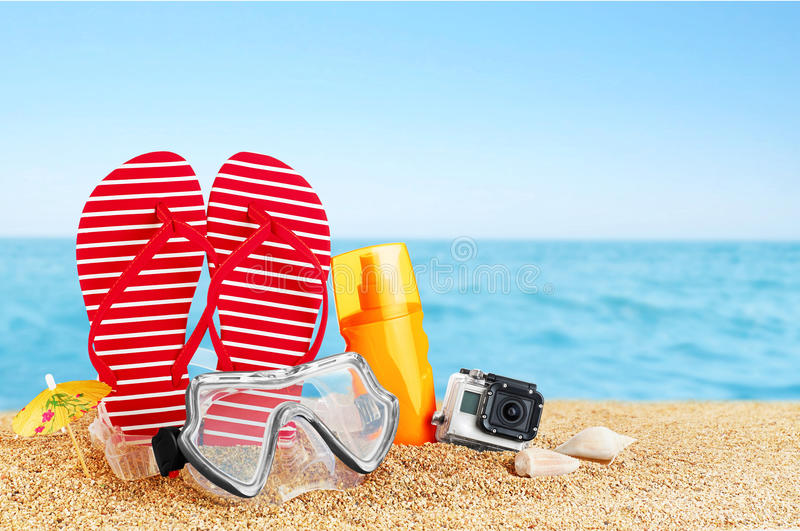 Flip-flops, sunscreen spray and diving masks on the beach. Shells and action camera royalty free stock photo