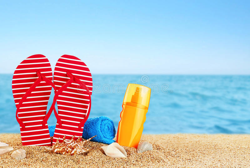 Flip-flops, sunscreen spray and towel on the beach. Shells royalty free stock photography
