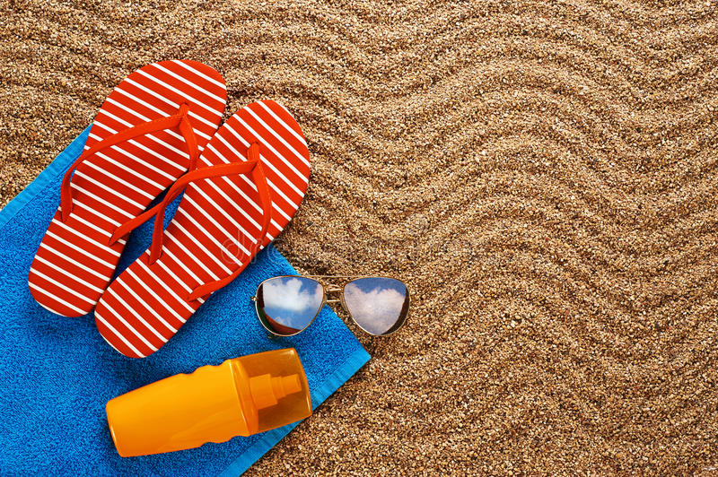 Flip-flops, sunscreen spray and towel on the beach. Sunglasses royalty free stock photography