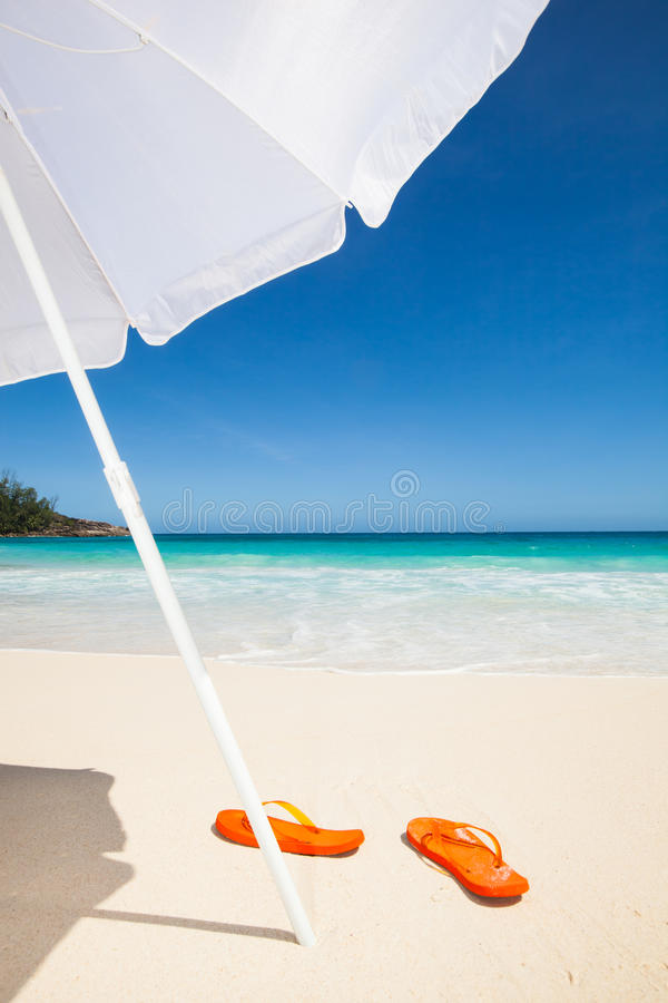 Flip-flops and sunshade stock photo