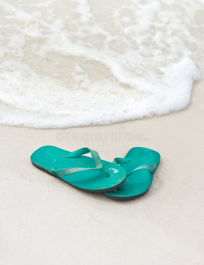 Flip Flops in the Surf. Blue-green flip flops (thong sandals) at the edge of the tide on a sandy beach stock image