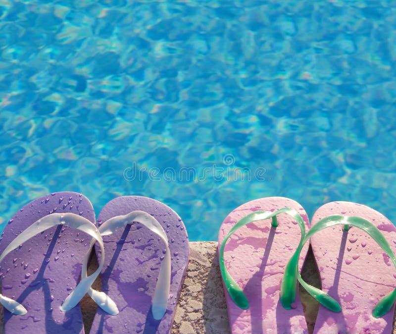 Flip flops beside swimming pool stock photo