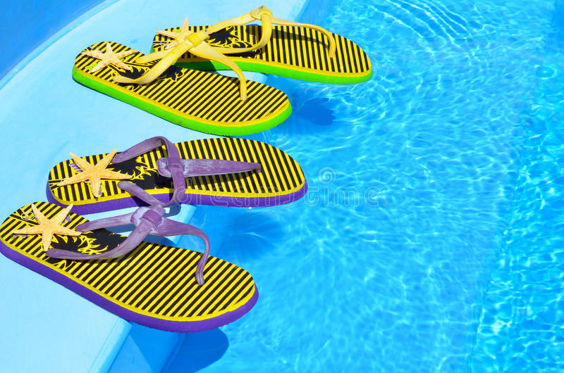 Flip-flops on the swimming pool. Flip-flops on the swimming blue pool royalty free stock images