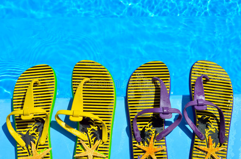 Flip-flops on the swimming pool. Flip-flops and starfish in the pool background royalty free stock photo