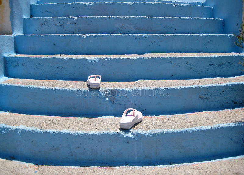 Flip-flops walking up the stairs. The scene has been shot on a windy beach of Rhodes island, in a hot sunny day royalty free stock photos