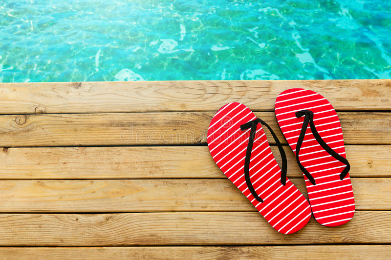 Flip flops on wooden deck over water background royalty free stock photo