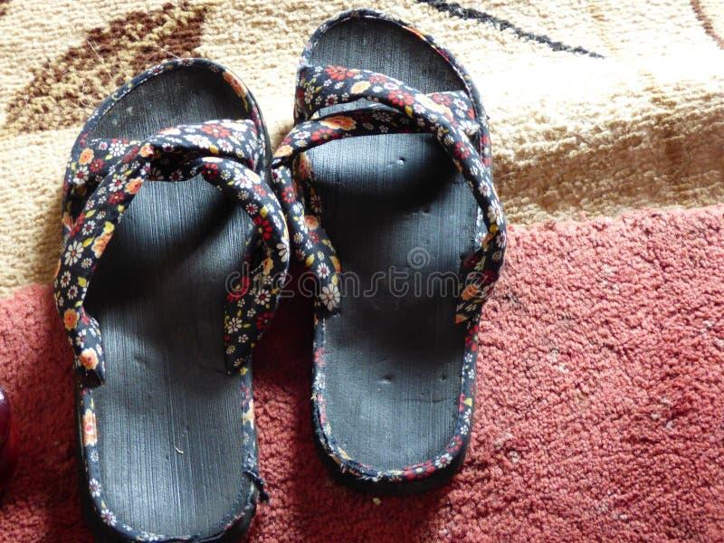Flip flops. Worn flip flops on red carpet royalty free stock images