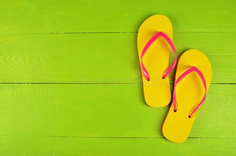 Flip Flops Yellow en fondo de madera verde foto de archivo