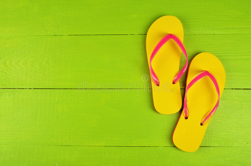 Flip Flops Yellow on green wooden background stock photo