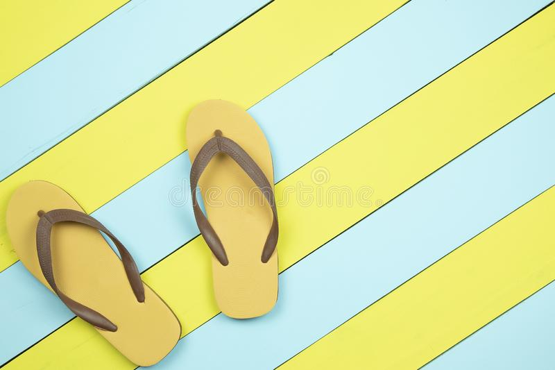 Flip flops on yellow and light green wooden background. royalty free stock image