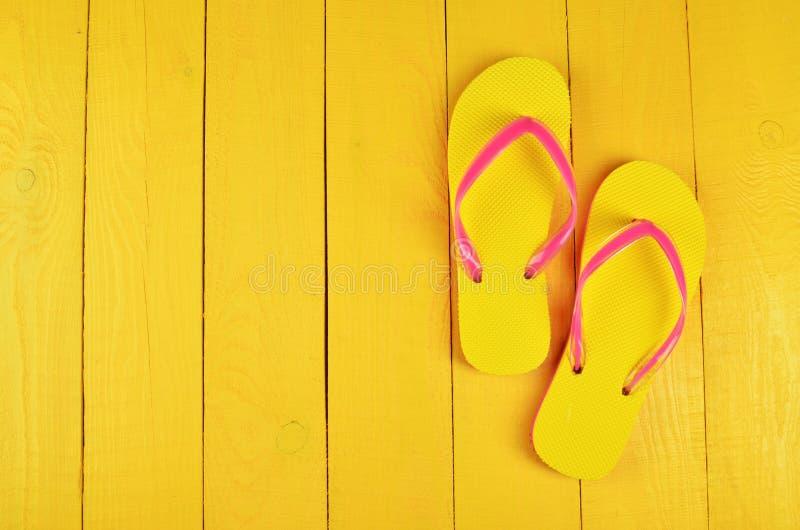 Flip Flops Yellow sur un fond en bois jaune photo stock