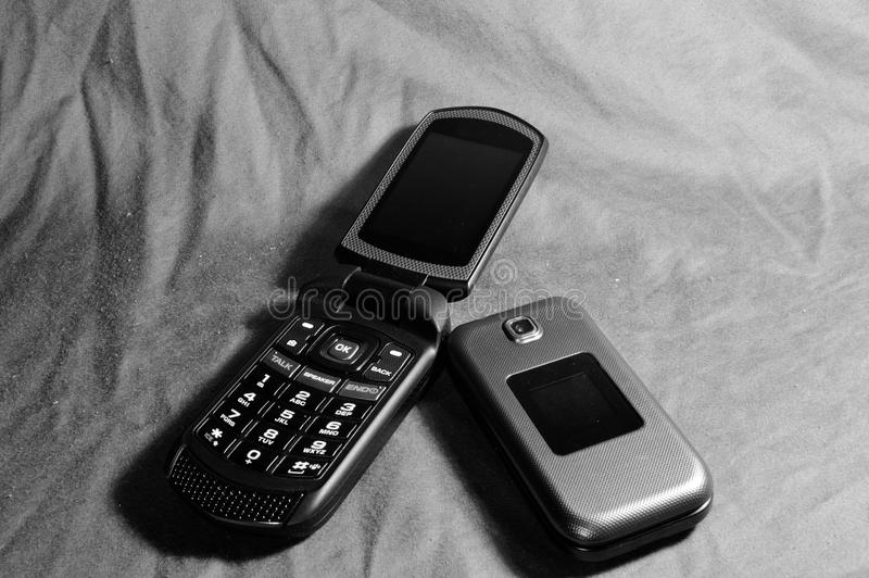 Flip Phones. Two flip phones, one open and one closed royalty free stock photos