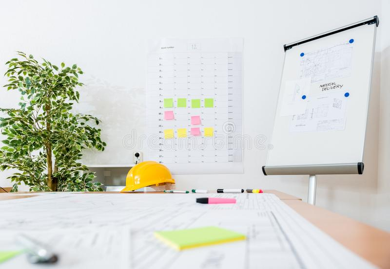 Flipchart And Yellow Hardhat At Workplace stock photos