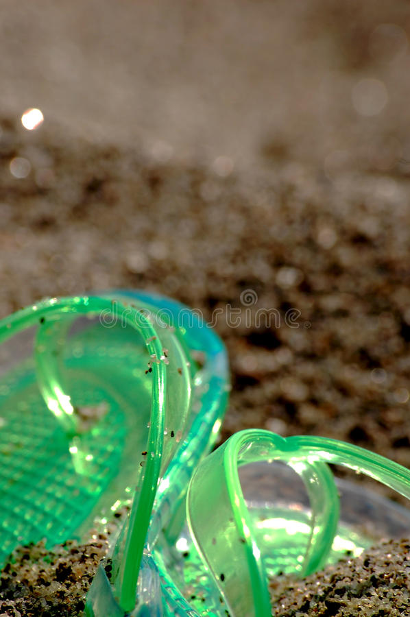 Flipflop in the sand. Green flipflop on a beach covered by sand royalty free stock image
