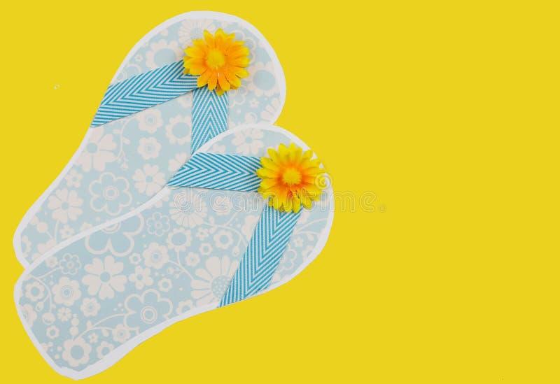 Flipflops des netten, Papierhandwerks, die Ozeanblau mit sonniger Seidenblumendekoration auf dem Zusammenbringen des gelben Hinte lizenzfreie stockbilder