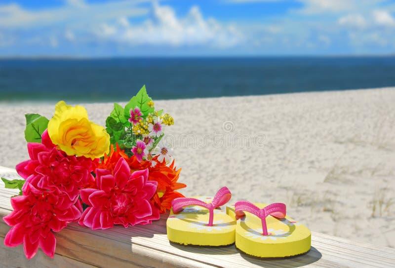 Flipflops und Blumen am Strand stockfotografie