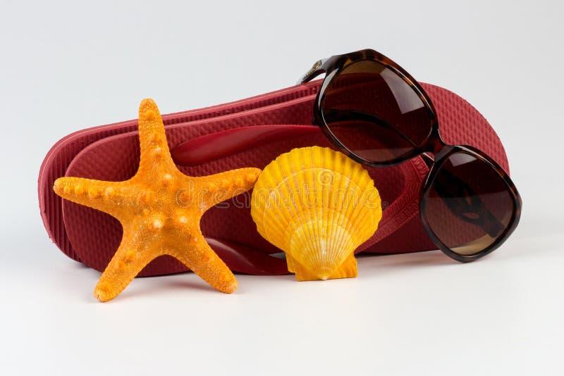 Flipflops und Sonnenbrille mit Oberteilen lizenzfreies stockbild