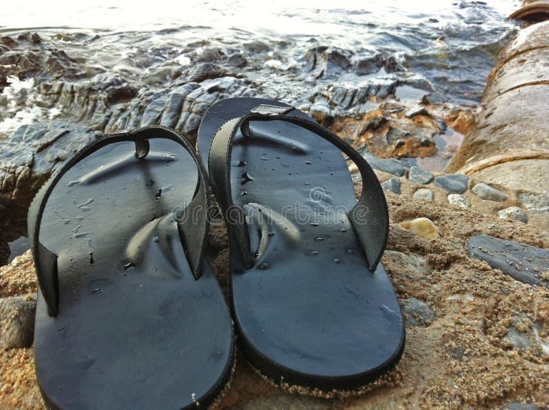 Flipflopschuhe setzten an Steinfront der Strand stockfotografie