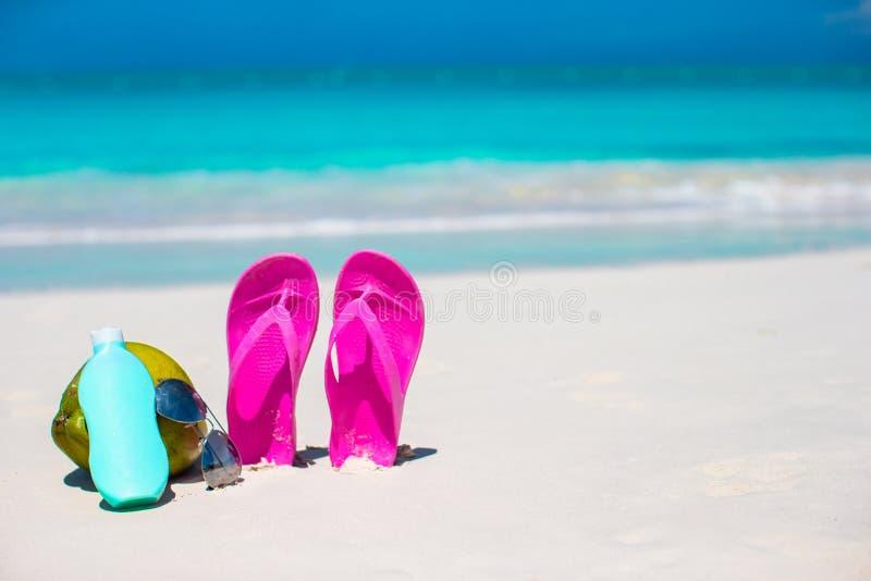 Flipmisslyckanden, kokosnöt och suncream på vit sand Begrepp av sommarsemestrar royaltyfri foto