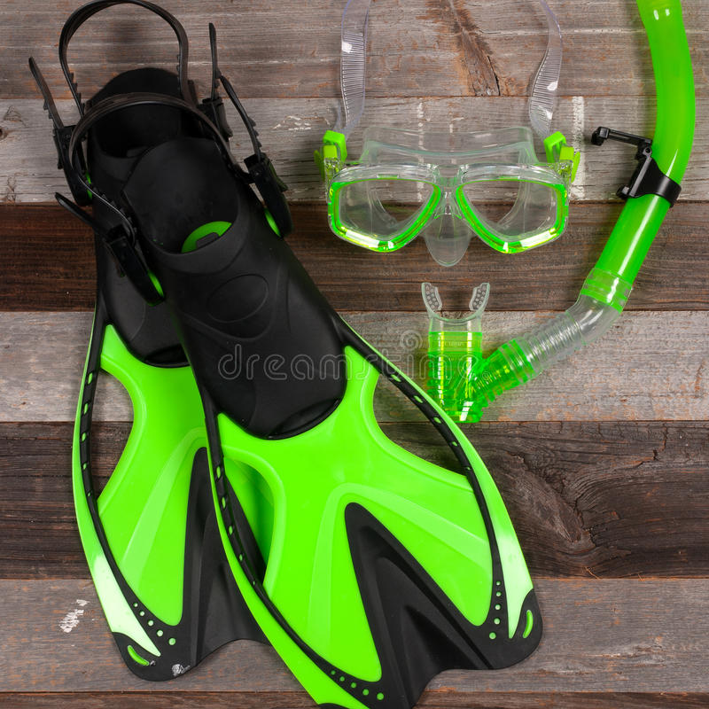 Flippers, mask and snorkel on a wood background. Snorkelling equipment. Flippers, mask and snorkel top view image royalty free stock photo